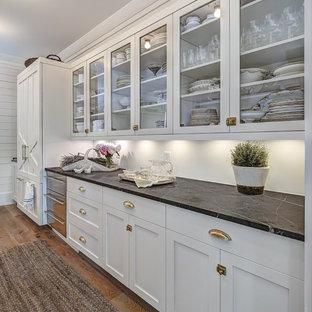 Exemple d'une grande cuisine américaine linéaire nature avec une crédence blanche, des portes de placard blanches, un plan de travail en marbre, un îlot central, un électroménager encastrable, un placard à porte shaker et un sol en bois brun.