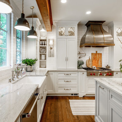 Inspiration for a mid-sized cottage u-shaped dark wood floor and brown floor eat-in kitchen remodel in Atlanta with white cabinets, quartzite countertops, white backsplash, an island, a farmhouse sink, subway tile backsplash, stainless steel appliances, shaker cabinets and white countertops