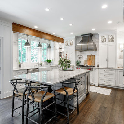 Eat-in kitchen - mid-sized farmhouse u-shaped dark wood floor and brown floor eat-in kitchen idea in Atlanta with white cabinets, quartzite countertops, white backsplash, an island, a farmhouse sink, shaker cabinets, subway tile backsplash, stainless steel appliances and white countertops