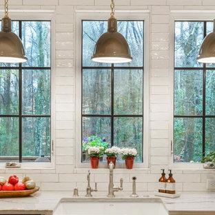 アトランタの中サイズのカントリー風おしゃれなキッチン (白いキャビネット、珪岩カウンター、白いキッチンパネル、エプロンフロントシンク、サブウェイタイルのキッチンパネル、シルバーの調理設備、濃色無垢フローリング、シェーカースタイル扉のキャビネット、茶色い床、白いキッチンカウンター) の写真
