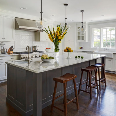 Inspiration for a large transitional dark wood floor kitchen remodel in Chicago with a single-bowl sink, recessed-panel cabinets, white cabinets, marble countertops, white backsplash, subway tile backsplash, stainless steel appliances and an island