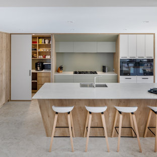 Large contemporary l-shaped kitchen in Perth with a double-bowl sink, quartz benchtops, green splashback, glass sheet splashback, black appliances, porcelain floors, with island, flat-panel cabinets, white cabinets, grey floor and white benchtop.