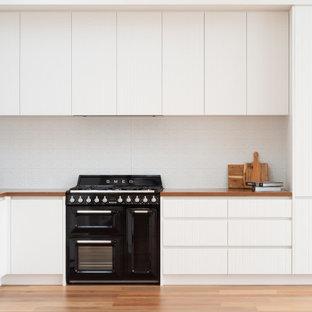 Small scandinavian l-shaped eat-in kitchen in Melbourne with a double-bowl sink, flat-panel cabinets, white cabinets, wood benchtops, white splashback, metal splashback, black appliances, medium hardwood floors, no island, brown floor, brown benchtop and vaulted.