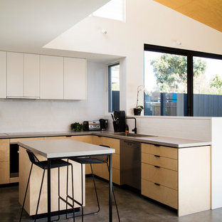 Contemporary l-shaped open plan kitchen in Melbourne with a drop-in sink, flat-panel cabinets, light wood cabinets, white splashback, stainless steel appliances, concrete floors, with island and grey floor.