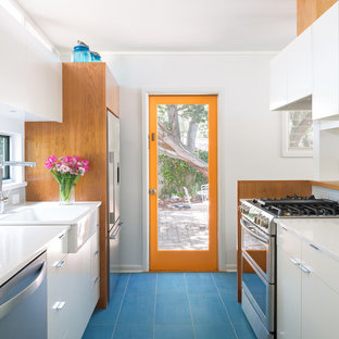 Small mid-century modern kitchen photos - Example of a small 1950s galley porcelain floor and blue floor kitchen design in Austin with a farmhouse sink, flat-panel cabinets, white cabinets, quartz countertops, white backsplash and ceramic backsplash