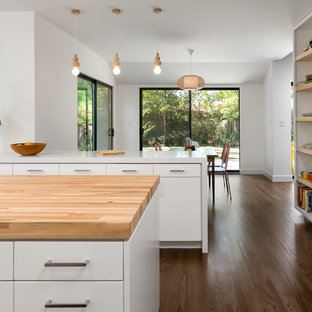Mid-sized midcentury u-shaped eat-in kitchen in Los Angeles with a double-bowl sink, flat-panel cabinets, white cabinets, wood benchtops, yellow splashback, ceramic splashback, stainless steel appliances, medium hardwood floors, with island and brown floor.