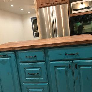 ソルトレイクシティの中くらいのシャビーシック調のおしゃれなキッチン (レイズドパネル扉のキャビネット、中間色木目調キャビネット、木材カウンター、ベージュキッチンパネル、シルバーの調理設備、セラミックタイルの床) の写真
