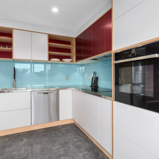 Photo of a mid-sized contemporary l-shaped eat-in kitchen in Wollongong with an integrated sink, flat-panel cabinets, stainless steel benchtops, blue splashback, glass sheet splashback, stainless steel appliances, vinyl floors, no island and grey floor.