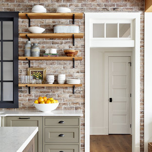 Foto på ett stort lantligt grå kök, med en rustik diskho, skåp i shakerstil, vita skåp, bänkskiva i kvarts, rött stänkskydd, stänkskydd i tegel, integrerade vitvaror, ljust trägolv och en köksö