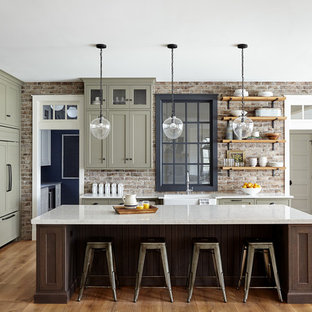 This is an example of a large country open plan kitchen in Philadelphia with a farmhouse sink, shaker cabinets, quartz benchtops, red splashback, brick splashback, panelled appliances, light hardwood floors, with island, green cabinets, beige floor and white benchtop.
