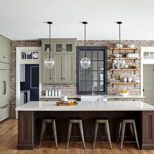 フィラデルフィアの大きいカントリー風おしゃれなキッチン (エプロンフロントシンク、シェーカースタイル扉のキャビネット、クオーツストーンカウンター、赤いキッチンパネル、レンガのキッチンパネル、パネルと同色の調理設備、淡色無垢フローリング、緑のキャビネット、ベージュの床、白いキッチンカウンター) の写真