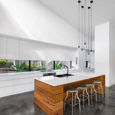 Kitchen - mid-sized contemporary galley concrete floor and gray floor kitchen idea in Melbourne with flat-panel cabinets, white cabinets, marble countertops, white backsplash, an island, white countertops, a double-bowl sink, window backsplash and stainless steel appliances