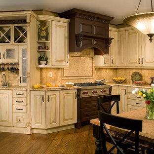 Idee per una grande cucina abitabile con ante con bugna sagomata, ante bianche, top in granito, paraspruzzi beige, paraspruzzi con piastrelle in ceramica, elettrodomestici da incasso, pavimento in legno massello medio e nessuna isola