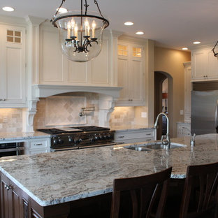 Large traditional eat-in kitchen ideas - Example of a large classic l-shaped dark wood floor eat-in kitchen design in Boston with a double-bowl sink, beaded inset cabinets, white cabinets, granite countertops, beige backsplash, stone tile backsplash, stainless steel appliances and an island