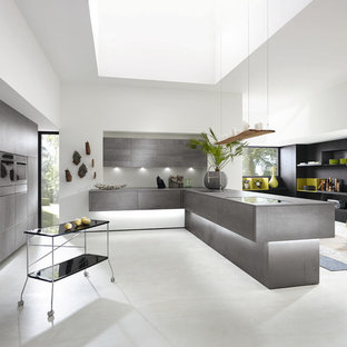 Inspiration for a mid-sized modern kitchen in New York with an undermount sink, grey cabinets, concrete benchtops, white splashback, cement tile splashback, concrete floors, with island and stainless steel appliances.