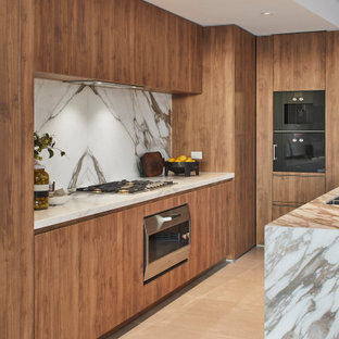 Mid-sized contemporary l-shaped kitchen in Sydney with flat-panel cabinets, medium wood cabinets, grey splashback, panelled appliances, porcelain floors, with island, beige floor and grey benchtop.