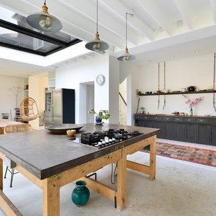 Idee per una cucina bohémian di medie dimensioni con ante con riquadro incassato, ante nere, top in cemento, elettrodomestici neri, pavimento in cemento, isola e pavimento grigio