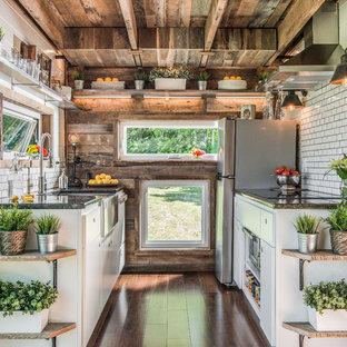 ナッシュビルのインダストリアルスタイルのおしゃれなキッチン (エプロンフロントシンク、フラットパネル扉のキャビネット、白いキャビネット、白いキッチンパネル、サブウェイタイルのキッチンパネル、パネルと同色の調理設備、濃色無垢フローリング、アイランドなし、茶色い床、グレーのキッチンカウンター) の写真