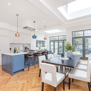 Inspiration for a classic galley kitchen/diner in London with a submerged sink, shaker cabinets, blue cabinets, white splashback, integrated appliances, medium hardwood flooring, an island, brown floors and white worktops.