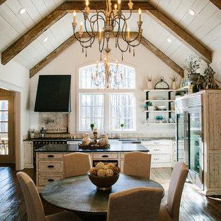 Zweizeilige, Mittelgroße Shabby-Style Wohnküche mit Schrankfronten im Shaker-Stil, weißen Schränken, Granit-Arbeitsplatte, Rückwand aus Travertin, braunem Holzboden und Kücheninsel in Atlanta