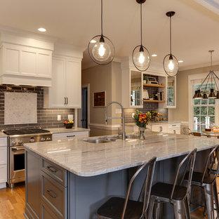 Mittelgroße Klassische Wohnküche mit Triple-Waschtisch, weißen Schränken, Granit-Arbeitsplatte, Küchenrückwand in Grau, Küchengeräten aus Edelstahl, Kücheninsel, grauer Arbeitsplatte, Schrankfronten im Shaker-Stil, Rückwand aus Metrofliesen und hellem Holzboden in Raleigh