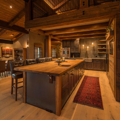 Eat-in kitchen - huge rustic l-shaped light wood floor eat-in kitchen idea in Other with a farmhouse sink, recessed-panel cabinets, wood countertops, gray backsplash, stainless steel appliances, an island and dark wood cabinets