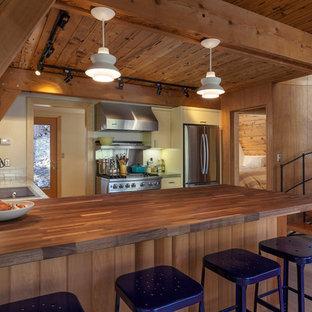 Rustikale Küche mit Waschbecken, flächenbündigen Schrankfronten, gelben Schränken, Arbeitsplatte aus Holz, hellem Holzboden und Halbinsel in Sacramento