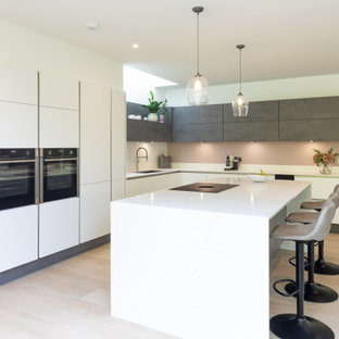 Photo of a large contemporary l-shaped kitchen/diner in Hampshire with a double-bowl sink, flat-panel cabinets, white cabinets, quartz worktops, white splashback, marble splashback, stainless steel appliances, porcelain flooring, an island, brown floors and white worktops.