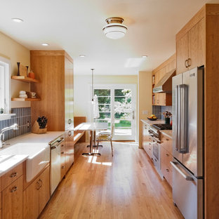 Design ideas for a modern galley eat-in kitchen in Portland with a farmhouse sink, medium wood cabinets, recycled glass benchtops, blue splashback, subway tile splashback, stainless steel appliances, flat-panel cabinets and light hardwood floors.