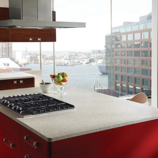 Modern eat-in kitchen in New York with red cabinets, recycled glass benchtops and stainless steel appliances.