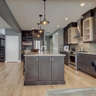 カルガリーの中サイズのエクレクティックスタイルのおしゃれなキッチン (淡色無垢フローリング、アンダーカウンターシンク、落し込みパネル扉のキャビネット、濃色木目調キャビネット、クオーツストーンカウンター、グレーのキッチンパネル、ガラスタイルのキッチンパネル、シルバーの調理設備、ベージュの床、グレーのキッチンカウンター) の写真