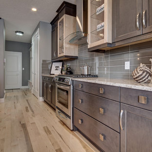 This is an example of a mid-sized eclectic l-shaped open plan kitchen in Calgary with light hardwood floors, an undermount sink, recessed-panel cabinets, dark wood cabinets, quartz benchtops, grey splashback, glass tile splashback, stainless steel appliances, with island, beige floor and grey benchtop.