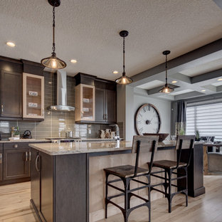 Design ideas for a mid-sized eclectic l-shaped open plan kitchen in Calgary with light hardwood floors, an undermount sink, recessed-panel cabinets, dark wood cabinets, quartz benchtops, grey splashback, glass tile splashback, stainless steel appliances, with island, beige floor and grey benchtop.