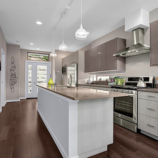 Small contemporary open concept kitchen appliance - Example of a small trendy galley medium tone wood floor open concept kitchen design in Seattle with an undermount sink, flat-panel cabinets, white cabinets, quartzite countertops, white backsplash, subway tile backsplash, stainless steel appliances and an island