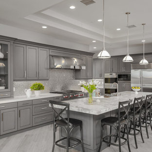 Transitional kitchen appliance - Inspiration for a transitional l-shaped kitchen remodel in San Diego with a farmhouse sink, shaker cabinets, gray cabinets, metallic backsplash, stainless steel appliances and an island