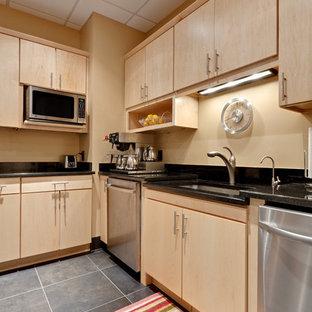 Cette image montre une grand cuisine américaine design en L avec un placard à porte plane, des portes de placard en bois clair, un sol gris, un évier encastré, un plan de travail en granite, une crédence noire, un électroménager en acier inoxydable, un sol en carrelage de porcelaine, un îlot central, une crédence en granite et un plan de travail noir.