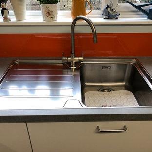 デヴォンのコンテンポラリースタイルのおしゃれなコの字型キッチン (シングルシンク、フラットパネル扉のキャビネット、白いキャビネット、ラミネートカウンター、オレンジのキッチンパネル、ガラス板のキッチンパネル、シルバーの調理設備、グレーのキッチンカウンター) の写真