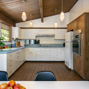 ロサンゼルスのミッドセンチュリースタイルのおしゃれなキッチン (アンダーカウンターシンク、フラットパネル扉のキャビネット、白いキャビネット、タイルカウンター、青いキッチンパネル、モザイクタイルのキッチンパネル、白い調理設備、アイランドなし、茶色い床、青いキッチンカウンター) の写真