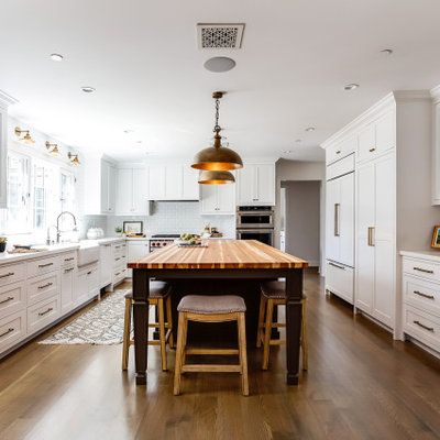 Inspiration for a mid-sized country l-shaped medium tone wood floor and brown floor kitchen remodel in Los Angeles with a farmhouse sink, shaker cabinets, white cabinets, quartz countertops, white backsplash, subway tile backsplash, stainless steel appliances, an island and white countertops