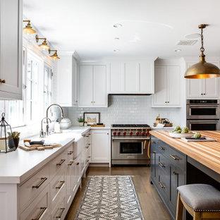 Geschlossene, Mittelgroße Landhausstil Küche in L-Form mit Landhausspüle, Schrankfronten im Shaker-Stil, weißen Schränken, Küchenrückwand in Weiß, Rückwand aus Metrofliesen, Küchengeräten aus Edelstahl, braunem Holzboden, Kücheninsel, braunem Boden, weißer Arbeitsplatte und Quarzwerkstein-Arbeitsplatte in Los Angeles