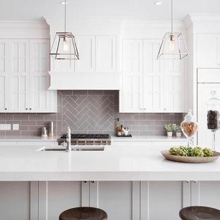 Cette image montre une cuisine traditionnelle avec un évier 2 bacs, un placard avec porte à panneau encastré, des portes de placard blanches, une crédence grise, une crédence en carrelage métro, un électroménager encastrable et un îlot central.