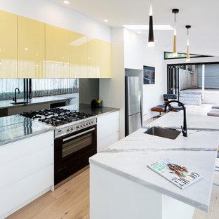 Zweizeilige Moderne Küche mit Unterbauwaschbecken, flächenbündigen Schrankfronten, gelben Schränken, Edelstahl-Arbeitsplatte, Küchenrückwand in Schwarz, Glasrückwand, Küchengeräten aus Edelstahl, braunem Holzboden, Kücheninsel, braunem Boden und grauer Arbeitsplatte in Newcastle - Maitland