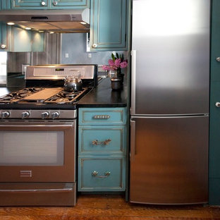 Contemporary kitchen designs - Example of a trendy kitchen design in New York with recessed-panel cabinets, blue cabinets, soapstone countertops, mirror backsplash and stainless steel appliances