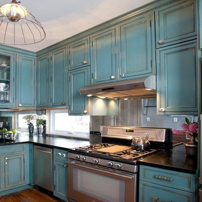 Elegant l-shaped enclosed kitchen photo in New York with stainless steel appliances, blue cabinets, soapstone countertops, mirror backsplash and beaded inset cabinets