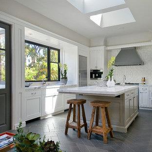 サンフランシスコのトランジショナルスタイルのおしゃれな独立型キッチン (落し込みパネル扉のキャビネット、白いキャビネット、大理石カウンター、白いキッチンパネル、シルバーの調理設備の、グレーの床) の写真