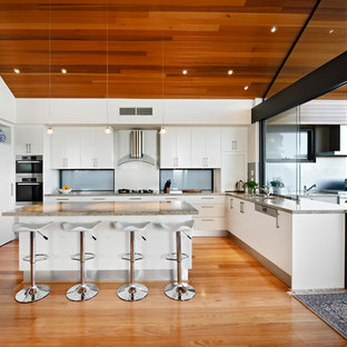 Inspiration for a large modern u-shaped medium tone wood floor eat-in kitchen remodel in Perth with stainless steel appliances, a drop-in sink, flat-panel cabinets, white cabinets, quartz countertops and an island