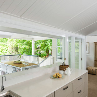 Mid-sized contemporary galley open plan kitchen in Brisbane with open cabinets, granite benchtops, white splashback, with island, white benchtop, a drop-in sink, carpet and beige floor.