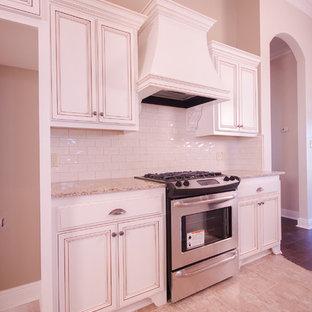 Ejemplo de cocina clásica con armarios con paneles lisos, encimera de madera, salpicadero blanco, salpicadero de azulejos tipo metro, electrodomésticos de acero inoxidable y suelo de baldosas de porcelana
