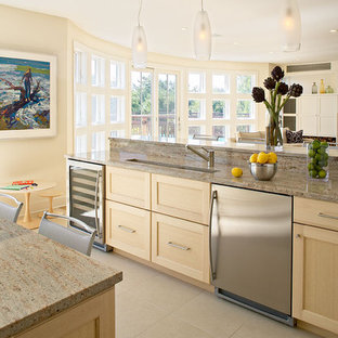 Example of a coastal open concept kitchen design in New York with stainless steel appliances, recessed-panel cabinets, light wood cabinets and granite countertops