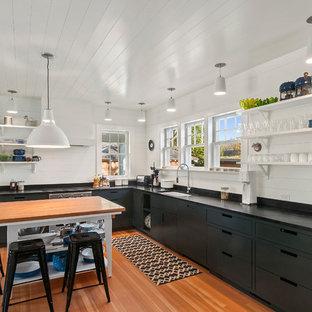 Idées déco pour une grande cuisine bord de mer en L avec un évier encastré, un placard à porte plane, des portes de placards vertess, un électroménager en acier inoxydable et un îlot central.
